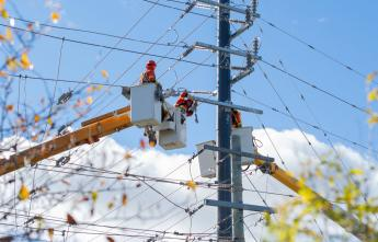 Powerline workers suspended in a bucket truck attend to a hydro pole